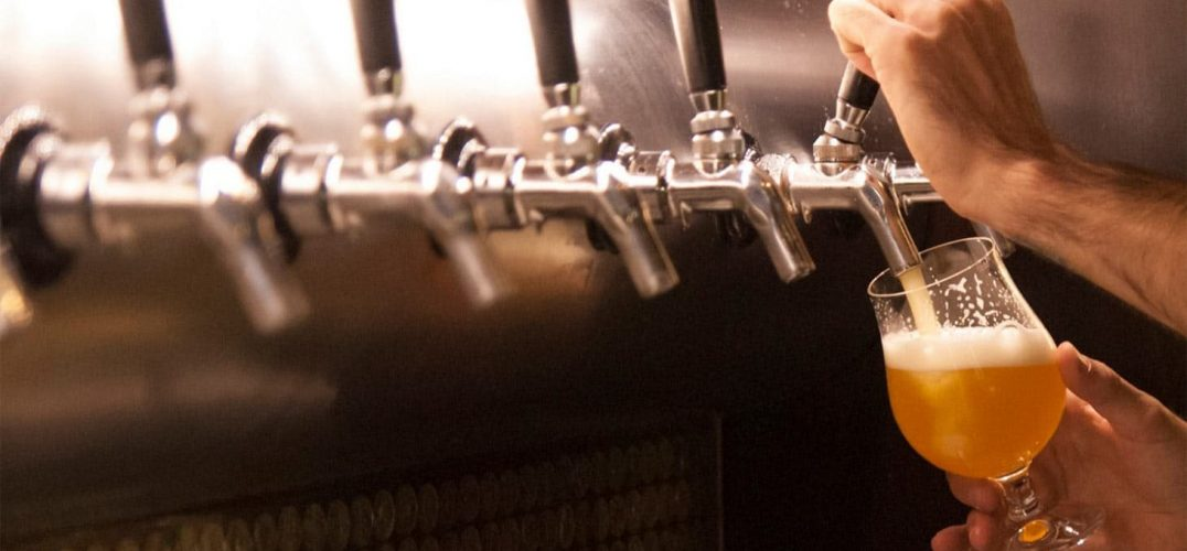 Man pouring a beer from a beer tap