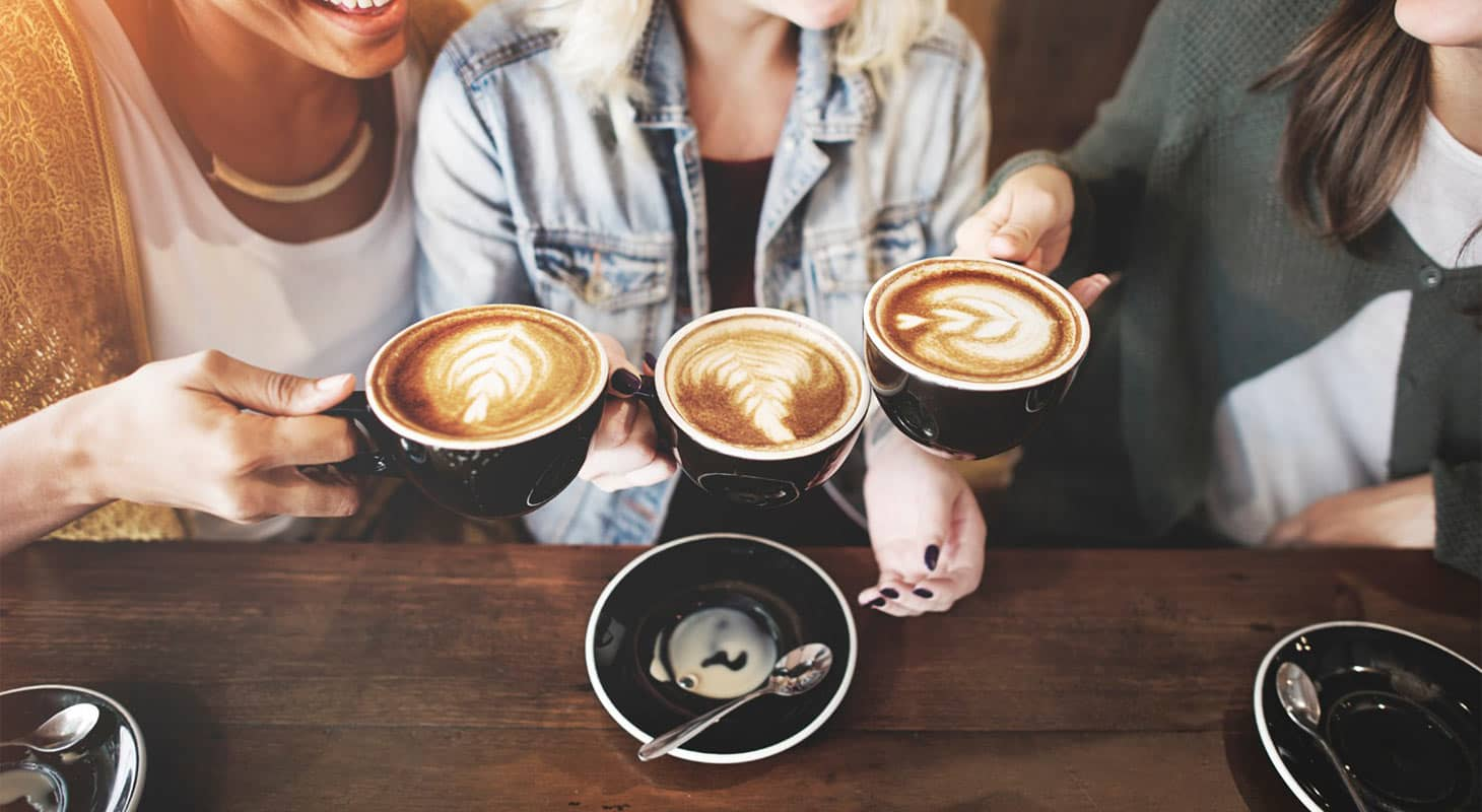 Three women holding mugs at a Placerville coffee shop