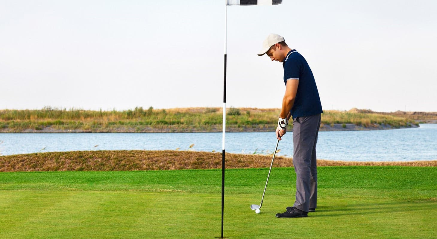 A young man putting at a Sacramento golf course