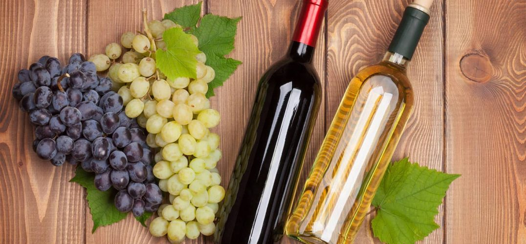 Bottle of white and red wine with grapes