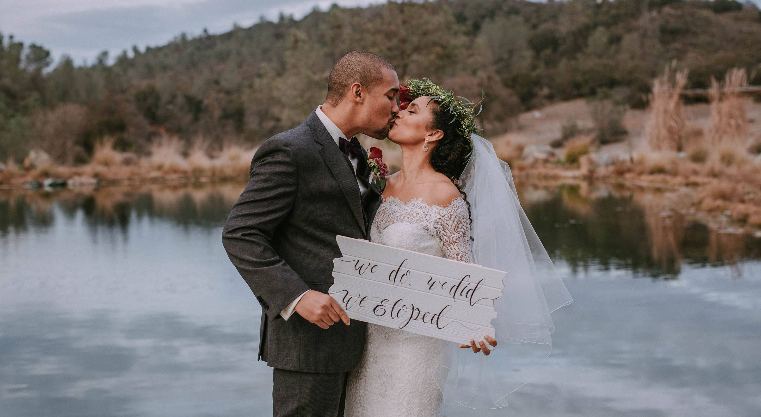 "Couple kissing in front of lake holding sign that says ""we do, we did, we eloped"""