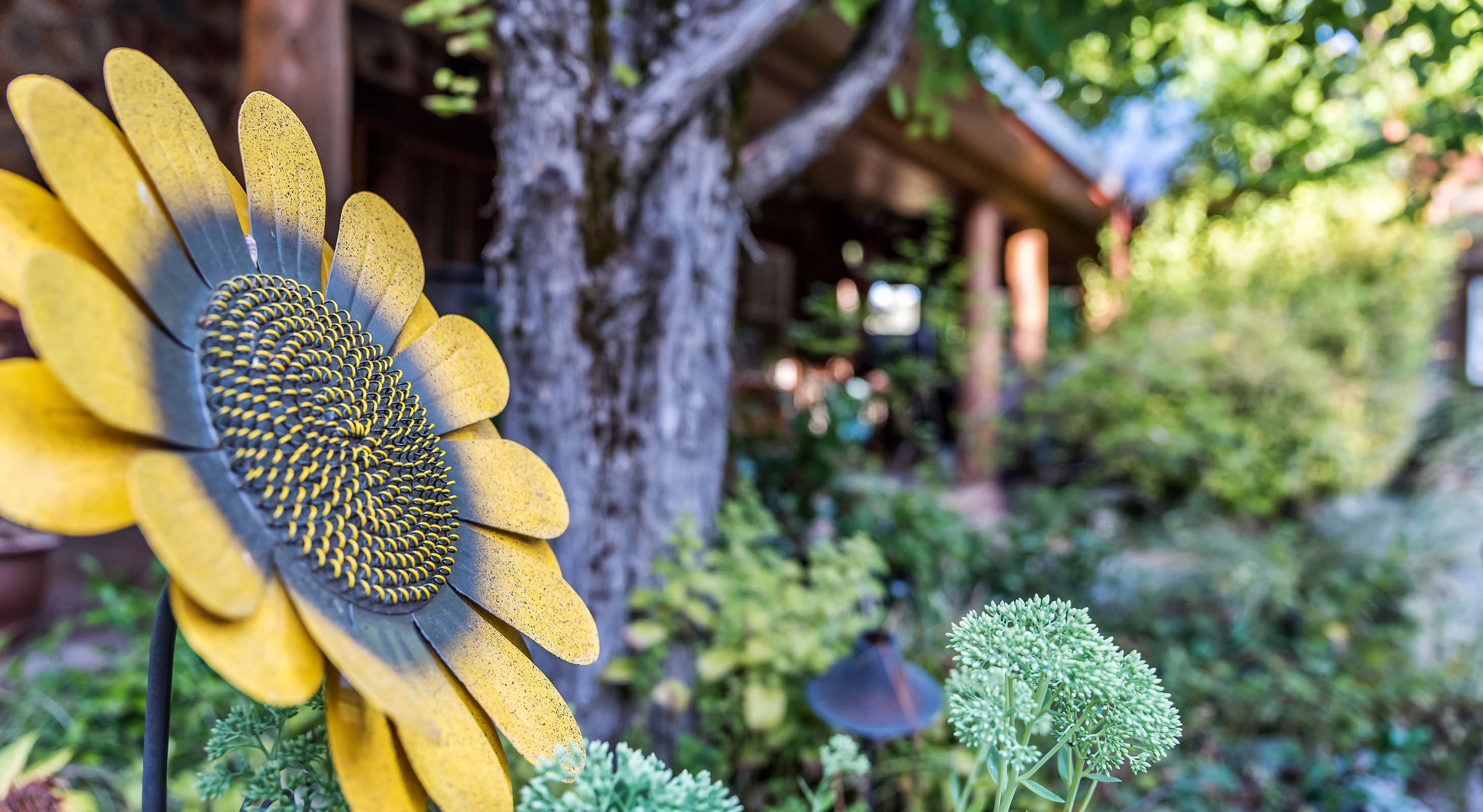 Metal sunflower decoration surrounded by foliage outdoors