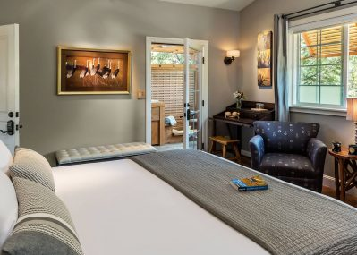 Plush bed across from sitting area in the Gray Pine room