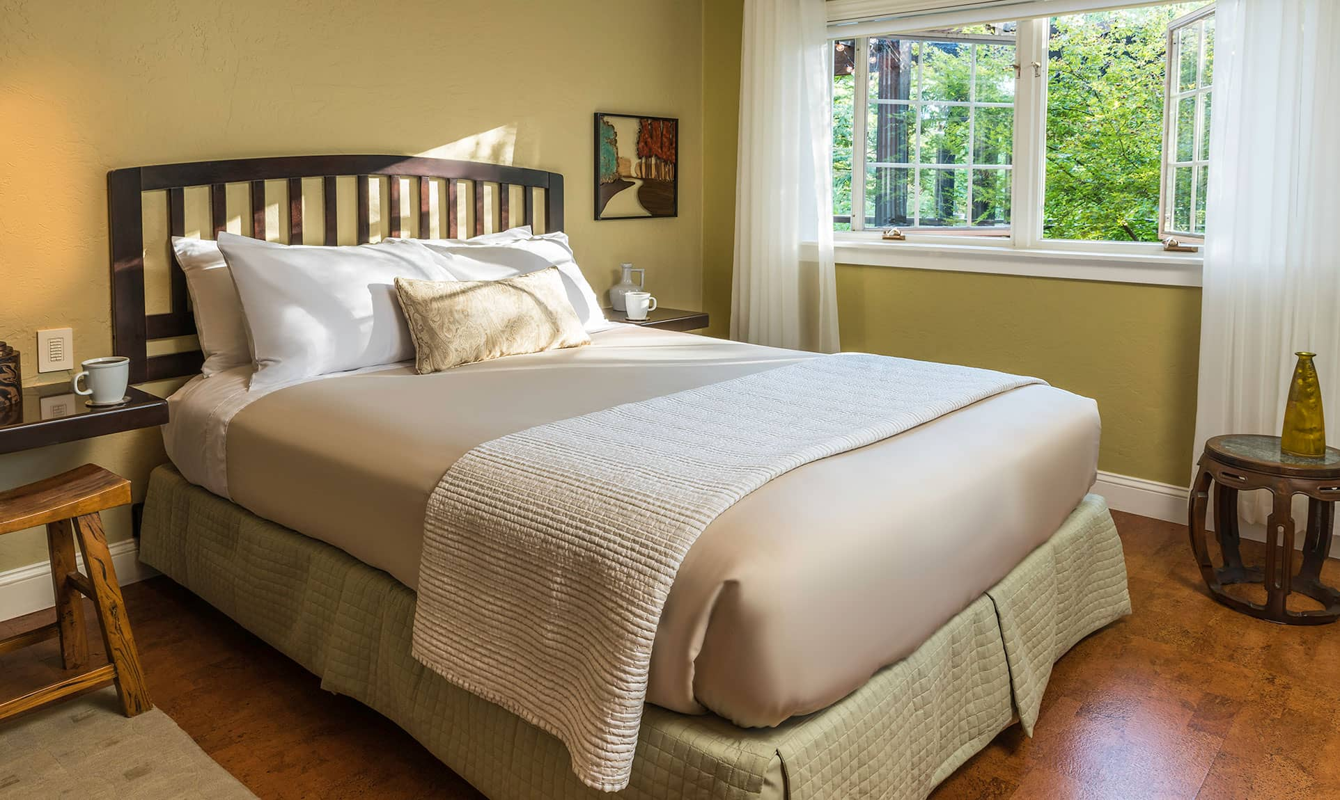 Comfortable bed by wide window in the Live Oak room
