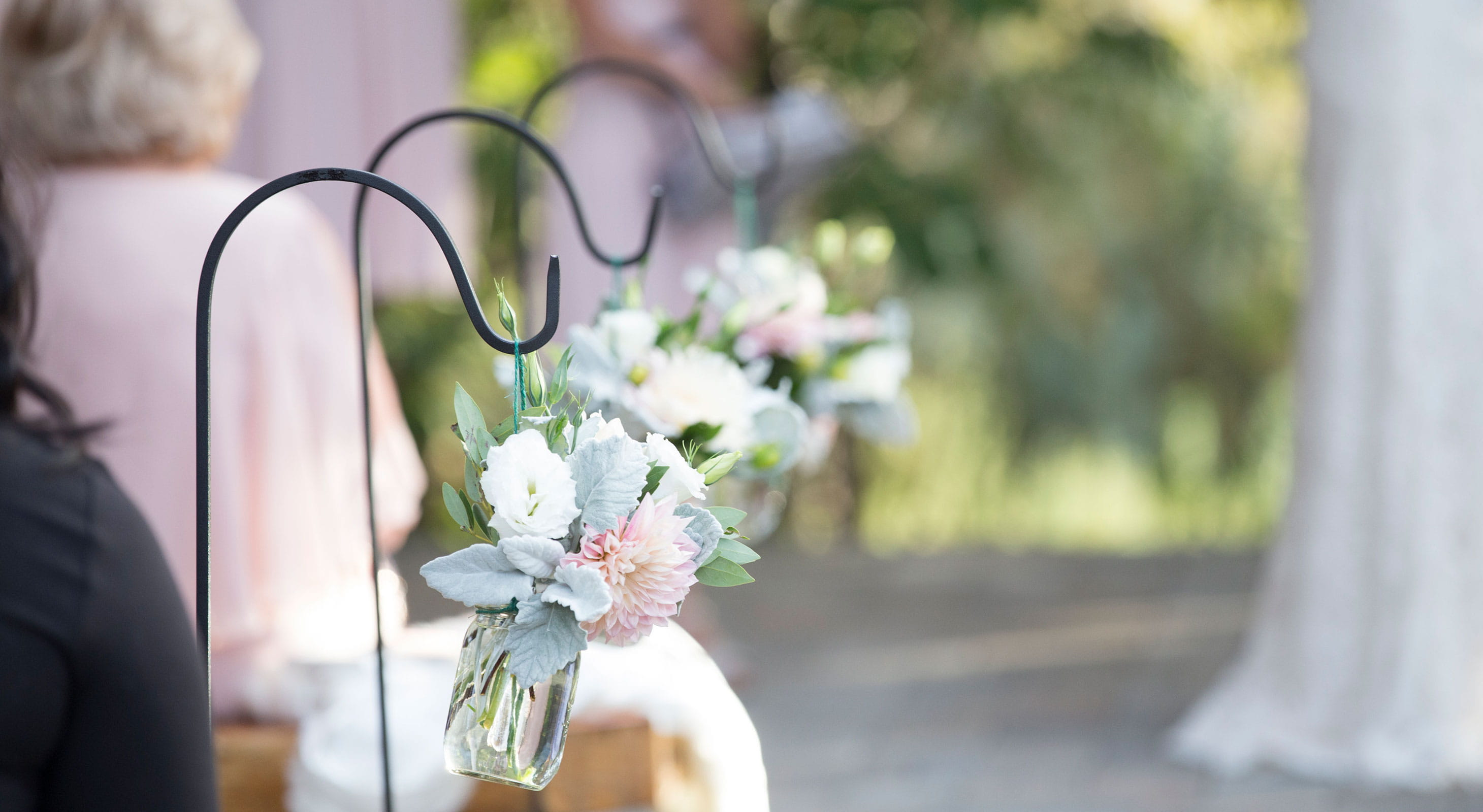 Hanging flower vases along the wedding aisle