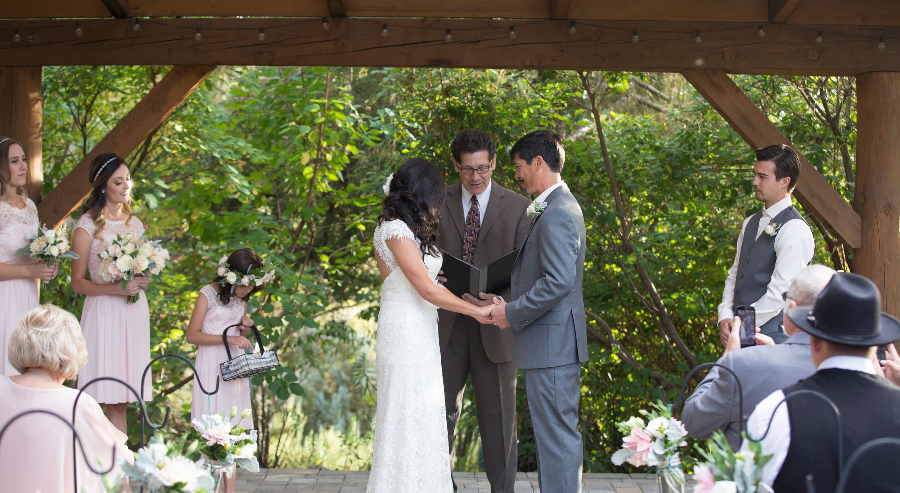 Couple exchanging vows under pavilion