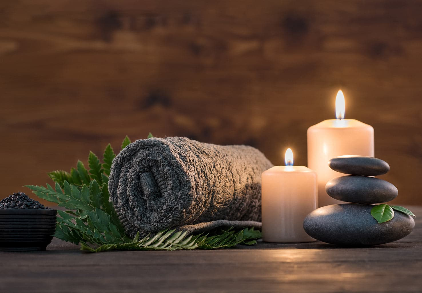hot stones with two candles and rolled towel