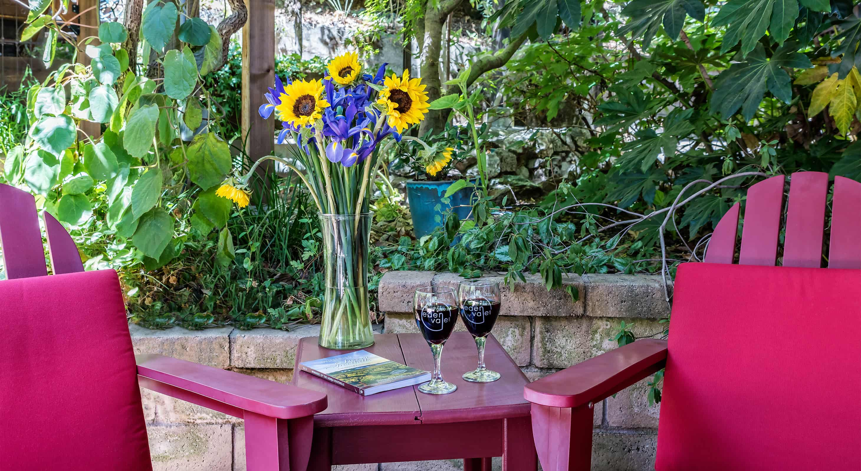 Vase of flowers with two glasses of red wine on patio