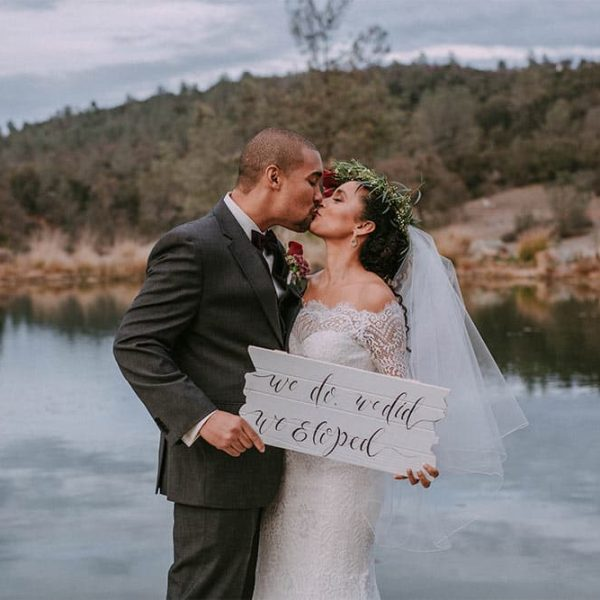 "Bride and Groom kissing by water holding sign that says ""We do, we did, We Eloped"""