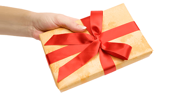 hand holding a gold wrapped gift box with red ribbon