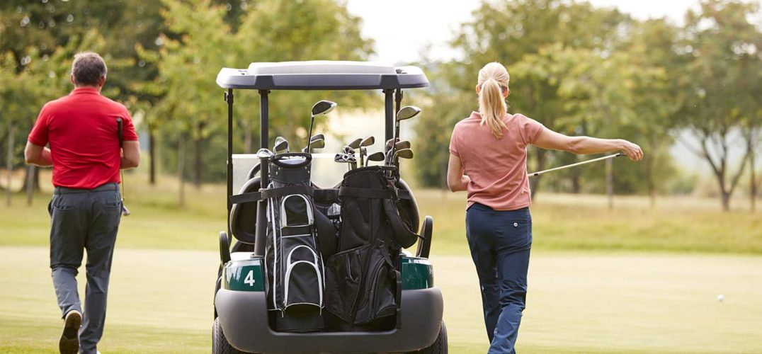 The back of a male and female golfer next to golf cart