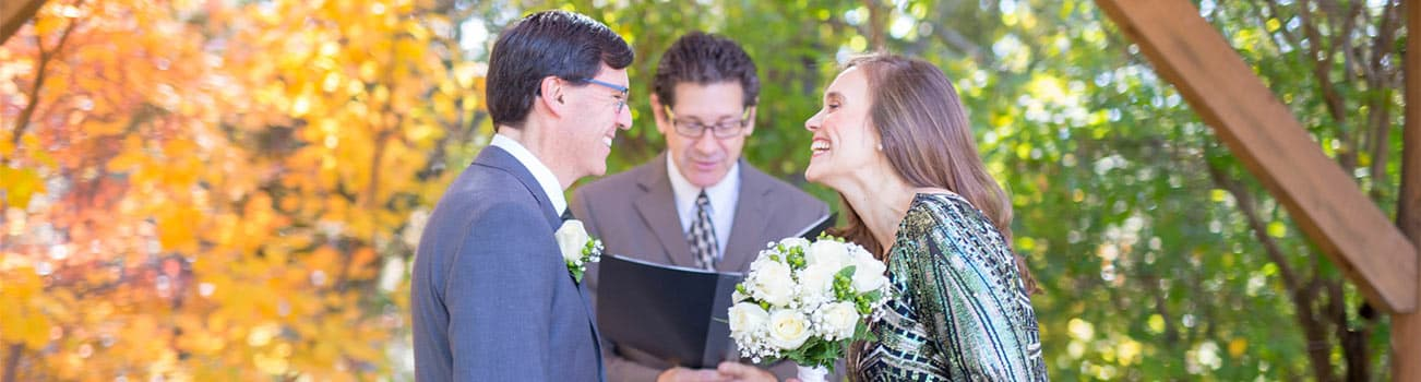 Smiling bride looking at groom during ceremony with officiant in background