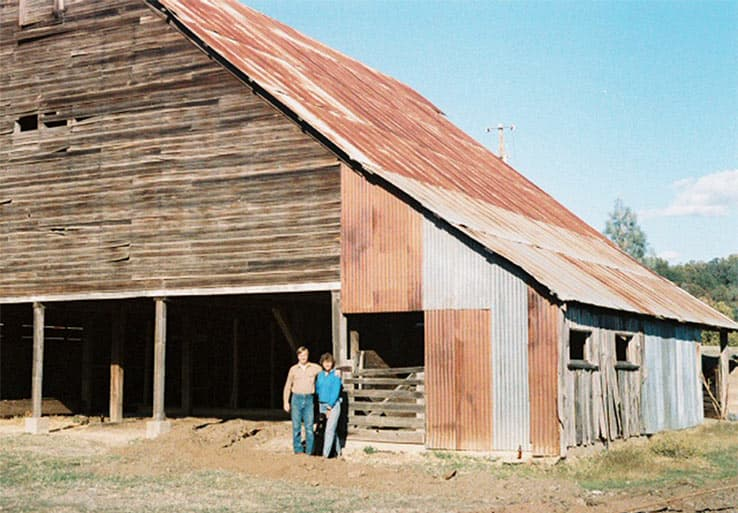 Historic photo of Mark and Gayle in front of Barn