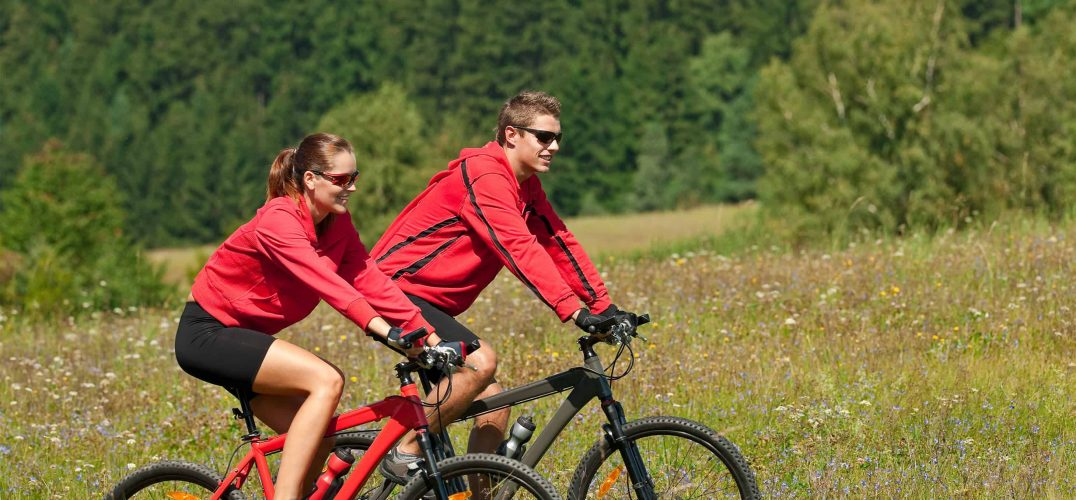 Couple outdoors riding mountain bikes