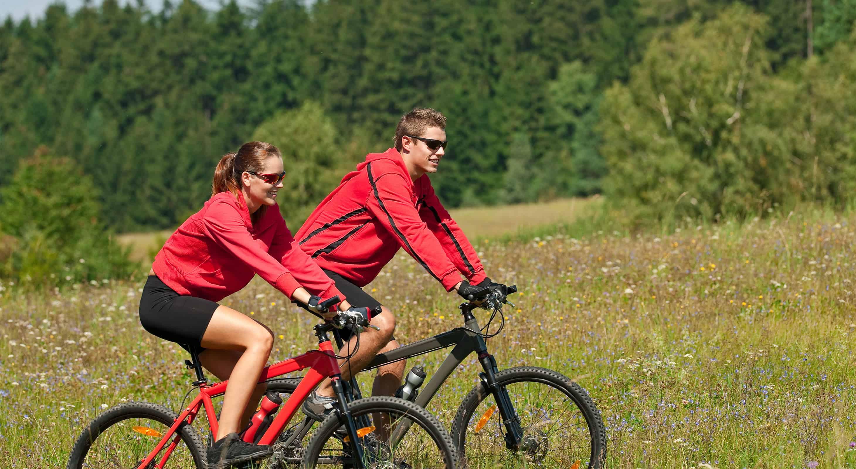Couple outdoors riding mountain bikes