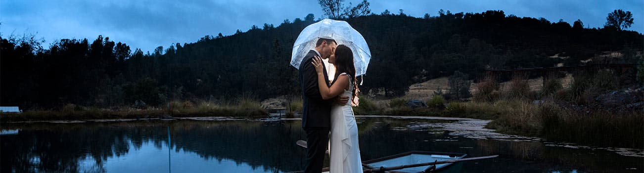 Wedding Kiss at the pond under a clear umbrella