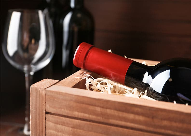 Bottle of Red wine in a wooden crate, wine glass in background