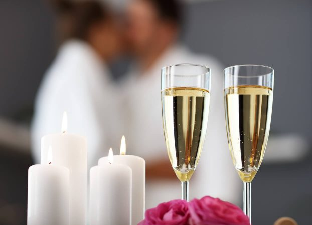 Champagne and candles in the foregrounds with a romantic couple blurred behind