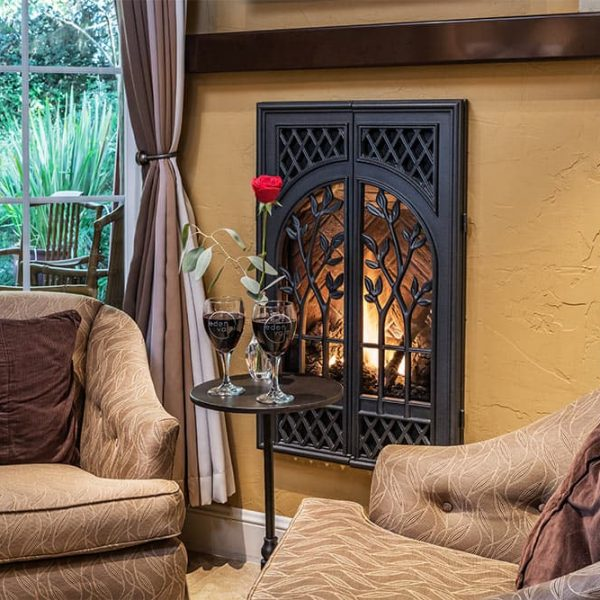 Fireplace in Stone Pine room with glasses of wine and single red rose