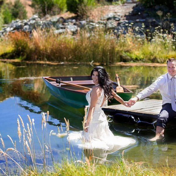 Bride in the pond with Groom on dock