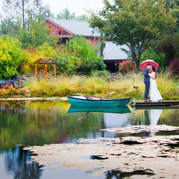 Bride and Groom under a red umbrella in front of our pond