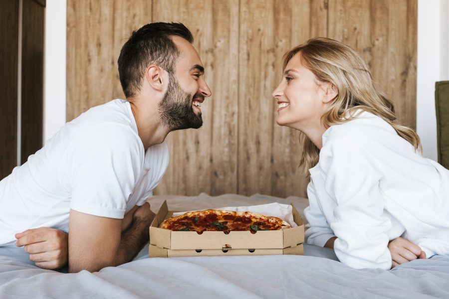 a man and woman eating pizza on a bed